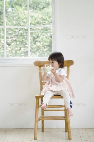 イスに座って水を飲んでいる女の子の写真素材 [FYI01705457]