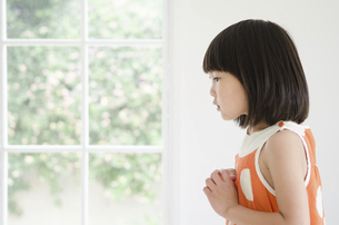 両手を胸に置いている女の子の横顔の写真素材 [FYI01705477]