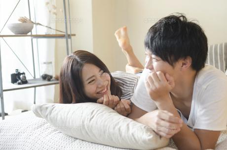 ベッドの上で笑うカップルの写真素材 [FYI01705506]