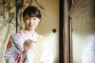 短冊に筆で俳句を書く着物姿の女性の写真素材 [FYI01705521]