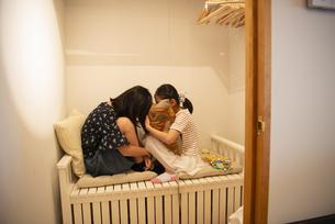 クローゼットの中で遊んでいる子供たちの写真素材 [FYI01705531]