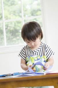 紙を切っている男の子の写真素材 [FYI01705535]