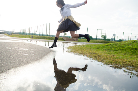 水たまりをジャンプする女子学生の写真素材 [FYI01705541]