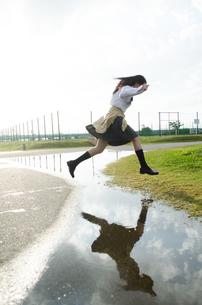 水たまりをジャンプする女子学生の写真素材 [FYI01705542]