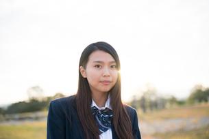 夕日を浴びている制服姿の女子高生の写真素材 [FYI01705572]