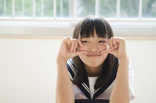 おちゃめなポーズをしている学生服の女の子の写真素材 [FYI01705586]