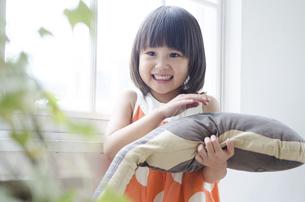 ギターのクッションを持って笑っている女の子の写真素材 [FYI01705587]