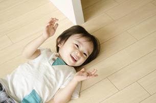 床に転がって笑っている男の子の写真素材 [FYI01705615]