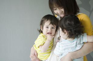 双子を抱っこする女性の写真素材 [FYI01705624]