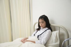 保健室のベッドにいる小学生の女の子の写真素材 [FYI01705627]
