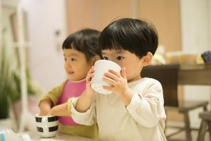 カップで飲み物を飲んでいる双子の写真素材 [FYI01705671]