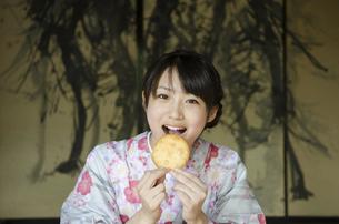 おせんべいを食べている着物姿の女性の写真素材 [FYI01705690]