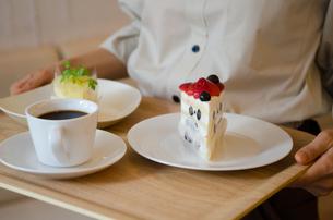 トレイに乗ったケーキとコーヒーを持っている女性の手元の写真素材 [FYI01705695]