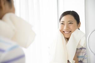 タオルで顔を拭いている女性の写真素材 [FYI01705711]