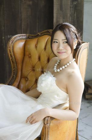 白いドレスを着てソファに座る女性の写真素材 [FYI01705740]
