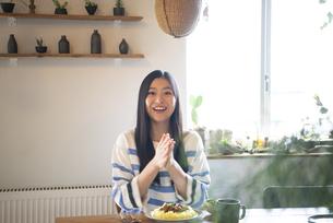 テーブルでご飯を食べようとしている女性の写真素材 [FYI01705749]