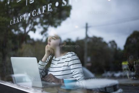 カフェでパソコンを開いてる窓ガラス越しの女性の写真素材 [FYI01705753]