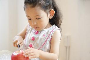 包丁でりんごを切っている女の子の写真素材 [FYI01705777]