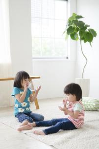 風船を膨らませている男の子と女の子の写真素材 [FYI01705786]