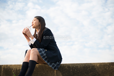 カップで何かを飲んでいる制服姿の女子高生の写真素材 [FYI01705796]