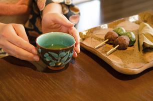 机にある和菓子と湯のみに添えられた着物姿の女性の手の写真素材 [FYI01705806]