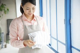 キッチンタオルを触っている女性の写真素材 [FYI01705818]