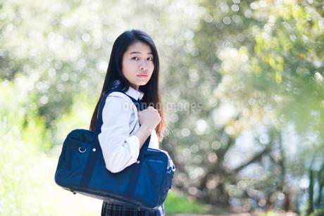 緑の中にいる制服姿の女子高生の写真素材 [FYI01705819]