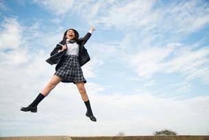 ジャンプをしている制服姿の女子高生の写真素材 [FYI01705842]