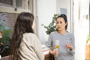 家で飲みながらおしゃべりをしている女性2人の写真素材 [FYI01705849]