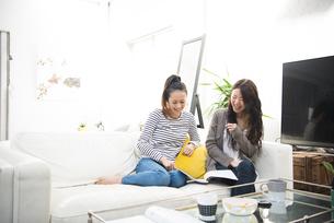 ソファの上でおしゃべりしている女性の写真素材 [FYI01705857]