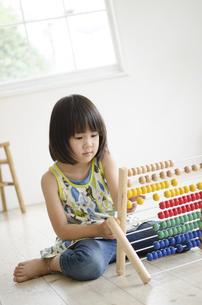 100玉そろばんで遊んでいる女の子の写真素材 [FYI01705860]