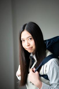 カバンを背負ってこちらを見る女子高生の写真素材 [FYI01705873]