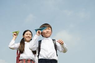 ランドセルを背負って紙飛行機を飛ばす子供たちの写真素材 [FYI01705874]