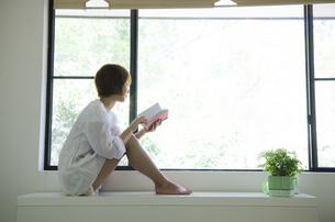窓際で本を読んでいる女性の写真素材 [FYI01705901]