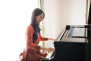 部屋でグランドピアノを弾いている女性の写真素材 [FYI01705903]