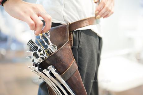 ハサミの入ったバッグを触っている美容師の写真素材 [FYI01705907]