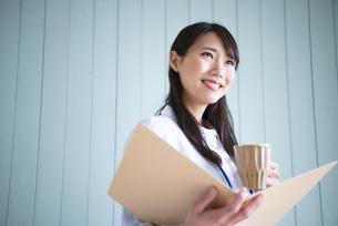 ファイルを開いてカップを持っている女性の写真素材 [FYI01705911]