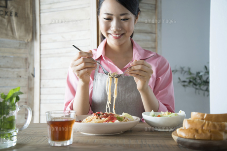 エプロンをしてパスタを食べようとしている女性の写真素材 [FYI01705917]