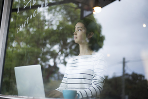 カフェでパソコンを開いてる窓ガラス越しの女性の写真素材 [FYI01705919]