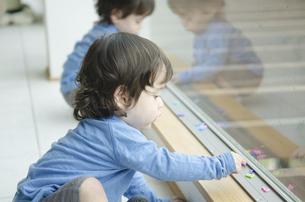 窓際で遊んでいる双子の男の子たちの写真素材 [FYI01705923]