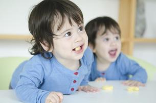 おやつを食べている双子の男の子たちの写真素材 [FYI01705930]