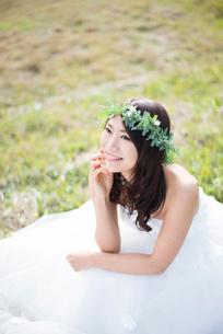 草の上に座るウェディングドレス姿の女性の写真素材 [FYI01705934]