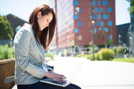 パソコンを持ってベンチに座っている女性の写真素材 [FYI01705960]