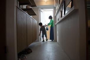 玄関で母親の手を引っ張っている男の子の写真素材 [FYI01705968]