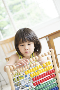 100玉そろばんで遊んでいる女の子の写真素材 [FYI01706008]