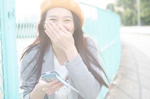 スマホを持って笑っている女性の写真素材 [FYI01706013]