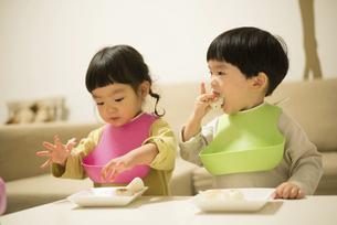 家でご飯を食べている双子の写真素材 [FYI01706019]