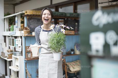 お花の鉢を持って笑っている女性の写真素材 [FYI01706024]