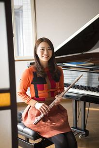 ピアノの前でフルートを持っている女性の写真素材 [FYI01706032]