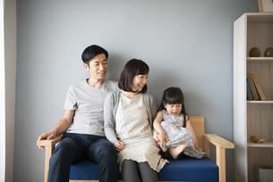 ソファに座っている三人家族の写真素材 [FYI01706062]
